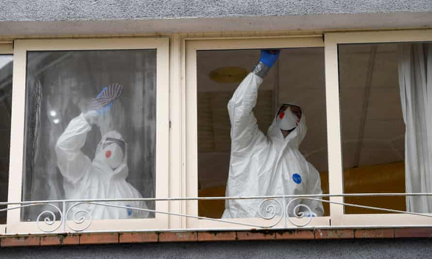 Workers clean a nursing home where a woman died and several residents and care workers were diagnosed with coronavirus in Grado, Asturias.