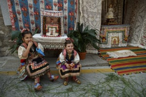 Girls sit next to an altar before the procession