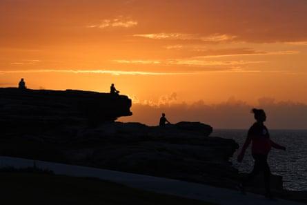 The sun rises as Sydneysiders practise social distancing in Maroubra.