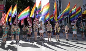Scouts carrying rainbow and American flags prepare to march.