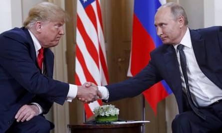 Donald Trump, left, and Vladimir Putin shake hands.