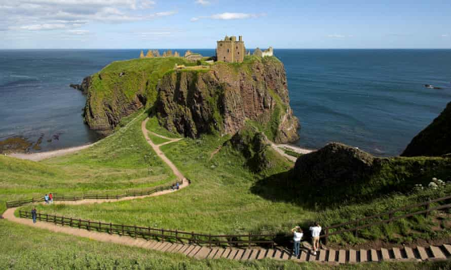 A view of Dunnottar castle, the path through grassland leading to it and the sea beyond