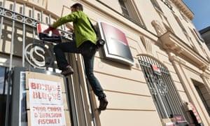 An activist hangs a sign that reads 'Bank blocked due to tax avoidance' during a protest in Le Mans against Société Générale