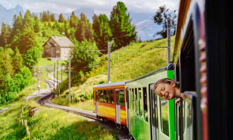 Little girl looking through the window of alpine train