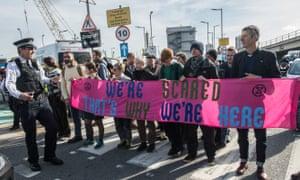 Climate crisis protestors block a road outside London City airport.