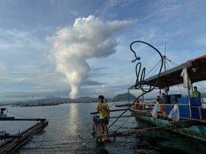 A villager boy throws a line next to the rumbling Taal Volcano as it emits smoke at a fishing village in Batangas province.