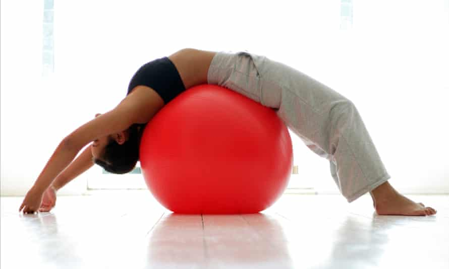 Young woman stretching on exercise ball