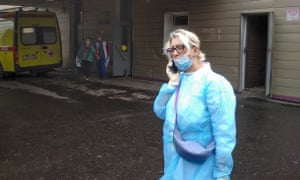 A medic speaks on the phone outside the hospital where Alexei Navalny is being treated in Omsk