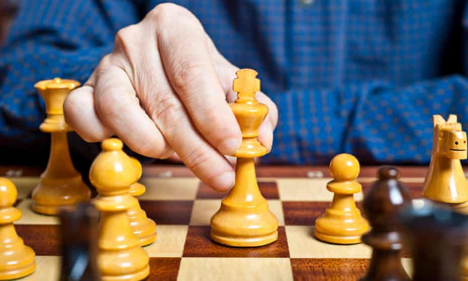 chess player hand playing a king move