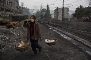 A woman carries goods to sell at a market across the railway tracks in the town of Shixi