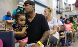 Caesar Mendez and his daughter Catalina wait inside the Corpus Christi Natatorium to board a bus to evacuate to San Antonio ahead of Hurricane Harvey.