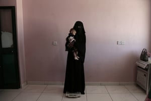 Umm Mizrah, a 25-year-old Yemeni woman, holds her son Mizrah on scales in Al-Sadaqa hospital.