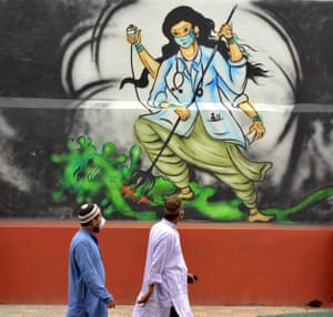 Two men walk past a graffito to honor medical workers who fight against the coronavirus in Guwahati, India.