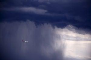 A Qantas Boeing 737-800 plane flies through heavy rain as the storm moves towards the city