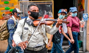 A Mariachi wears a face mask as he perform on the street to earn some money due to the lack of work amid the COVID-19 novel coronavirus pandemic, in Mexico City. Latin America and the Caribbean surpassed Europe on Friday to become the region hardest-hit by coronavirus deaths.