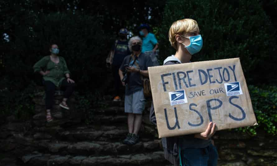 A group of protesters hold a demonstration in front of Postmaster General Louis DeJoy's home in Greensboro, North Carolina on Sunday.