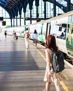 A young lady is walking on the train platform