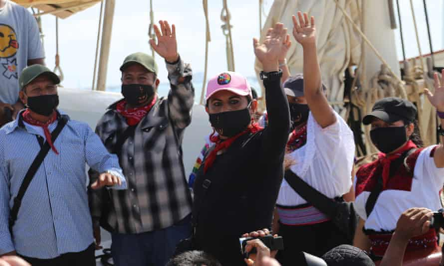 Members of the Zapatista Army of National Liberation (EZLN) wave goodbye as they set sail for Europe from Isla Mujeres, Mexico