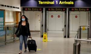 A passenger wearing a face mask comes through the arrival terminal at Manchester Airport.