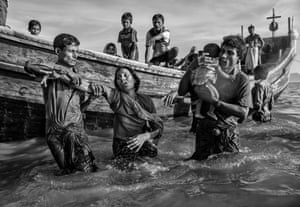 Refugees are helped from a boat as they arrive exhausted on the Bangladesh side of the Naf river at Shah Porir Dwip