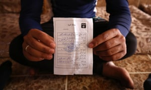 A former Iraqi Army member holds the 'repentance card' he received from Islamic State after militants took over his home in Eski Mosul, northern Iraq.