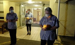 Nursing staff at the Langholme Care Home stand together and hold candles at 8pm.