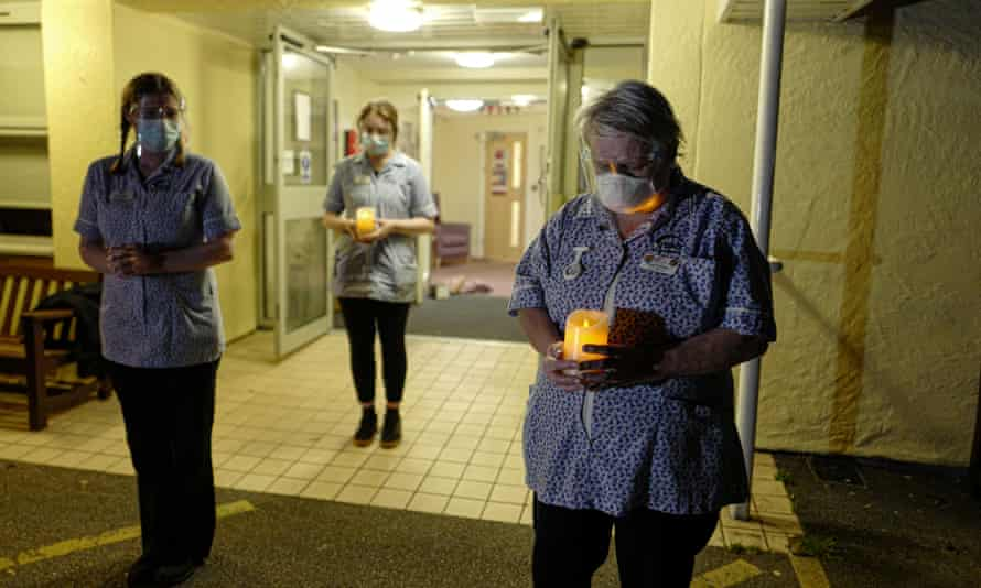 Nursing staff at a care home in Cornwall hold candles in March to mark a year since the beginning of the coronavirus pandemic