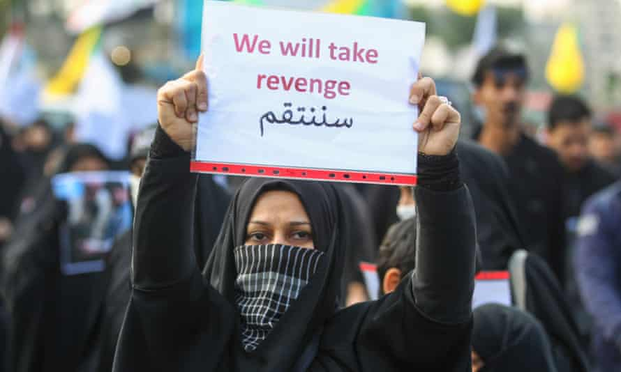 An Iraqi woman holds a placard during the funeral of Iranian military commander Qassem Suleimani, Iraqi paramilitary chief Abu Mahdi al-Muhandis and eight others in Baghdad on n 4 January.