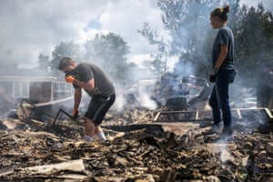 Josh Whitlock and Stacy Mathieson look through what is left of their home after it burned following the flood.
