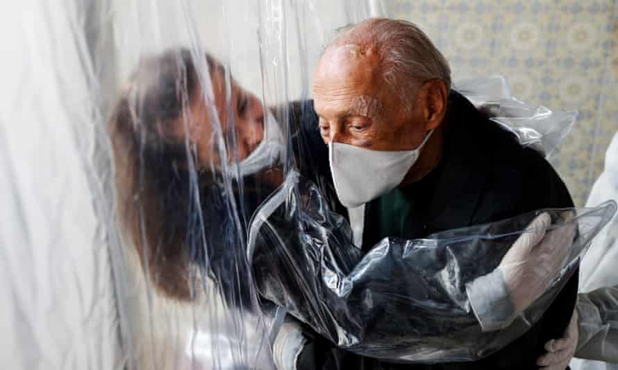 A woman hugs her father through a plastic curtain at a care home in São Paulo, Brazil.