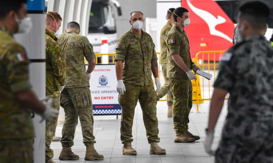 Australian Defence Force members wait for passengers to arrive for hotel quarantine at Sydney airport in August 2020