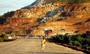 A Malagasy worker is dwarfed by a scarred hillside where Rio Tinto is constructing an ilmenite mine at Fort Dauphin