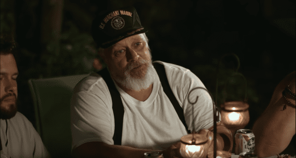 Flanigan's father, at the dinner table in, in braces and a US Marines cap