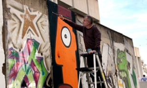 Thierry Noir repainting part of the original Berlin Wall in 2009 outside the Wende Museum in Los Angeles