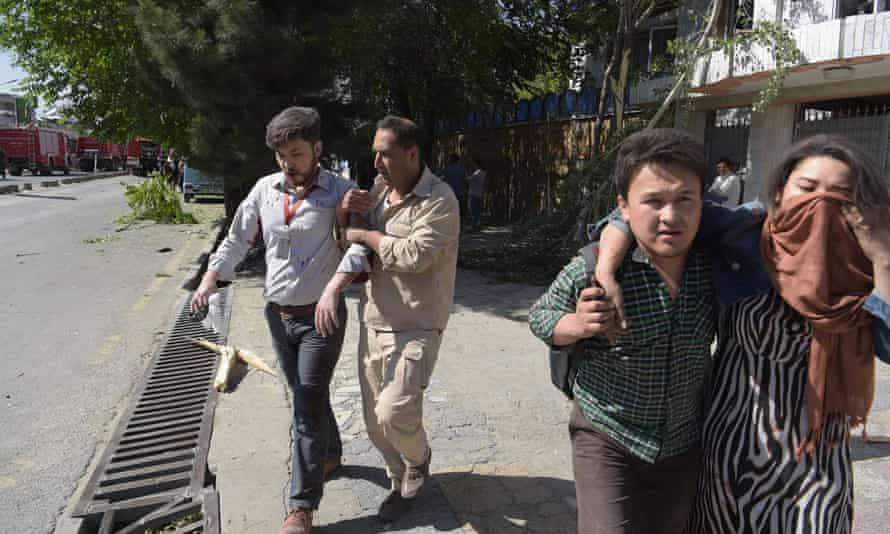 Afghan men provide assistance to the wounded at the site of a car bomb attack in Kabul on 31 May 2017.