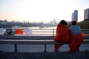 Two protesters wrapped in sleeping bags watch the sun rise over the city as they enter day five of action