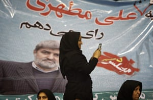 A woman snaps pictures with her mobile phone in front of a campaign poster that rads 'I will vote for Ali Motahari'.