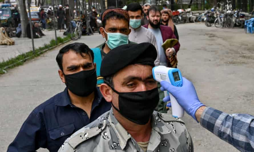A health worker checks the body temperature of men waiting for Friday prayers outside a mosque in Kabul.