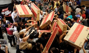 Shoppers reach for television sets at a store in Sao Paulo, Brazil