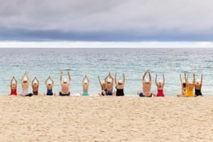Participants take part in a group meditation session as part of a surrealist art installation at North Cottesloe beach in Perth, Australia