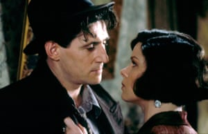 Marcia Gay Harden holding Gabriel Byrne's jacket lapel as they look at each other