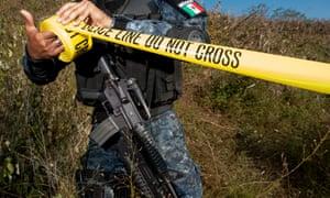 A mexican policeman unrolls crime scene tape