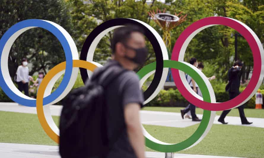 People walk near the Olympic Rings in Tokyo