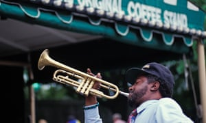 A street musician plays the trumpet outside a coffee house in the French Quarter of New Orleans.