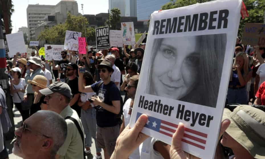 A demonstrator holds up a picture of Heather Heyer during a demonstration in front of city hall for victims of the Charlottesville attack on 13 August 2017.