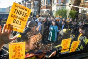 London, UK. Liberal Democrat leader Jo Swinson speaks to Extinction Rebellion protesters dressed as bees after they glued themselves to the party's battle bus during a visit to Knights youth centre