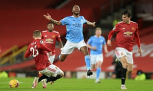 Manchester City's Raheem Sterling reacts under pressure from Luke Shaw and Victor Lindelof of Manchester United.