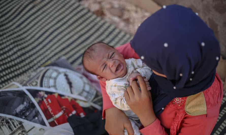 A mother and her baby at the Idlib camp, near the Bab al-Hawa border gate, Syria 30 June
