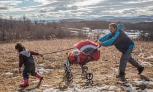 Hasan, 52, from Afghanistan, pushes his baby daughter through the snowy trails near Bosnia's border with Croatia.