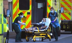 An ambulance crew wear PPE as they deal with a patient at Royal London hospital.
